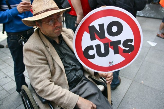disabled-man-holding-no-cuts-sign-640x427