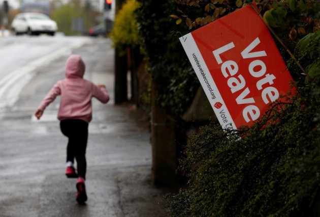A girl runs past a Vote Leave sign, protruding from the garden of a house in Altrincham